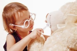 Cute little child girl playing dentist with teddy bear (Children's dentistry, health, medicine concept)