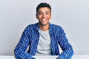Young handsome african american man wearing casual clothes sitting on the table looking positive and happy standing and smiling with a confident smile showing teeth
