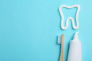 Tooth made of paste, tube, brush and space for text on color background, flat lay