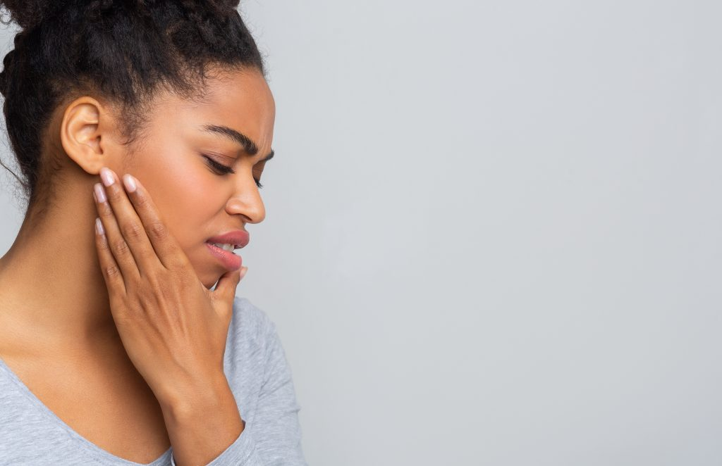 Young afro woman having acute toothache, holding her jaw, copy space, grey background
