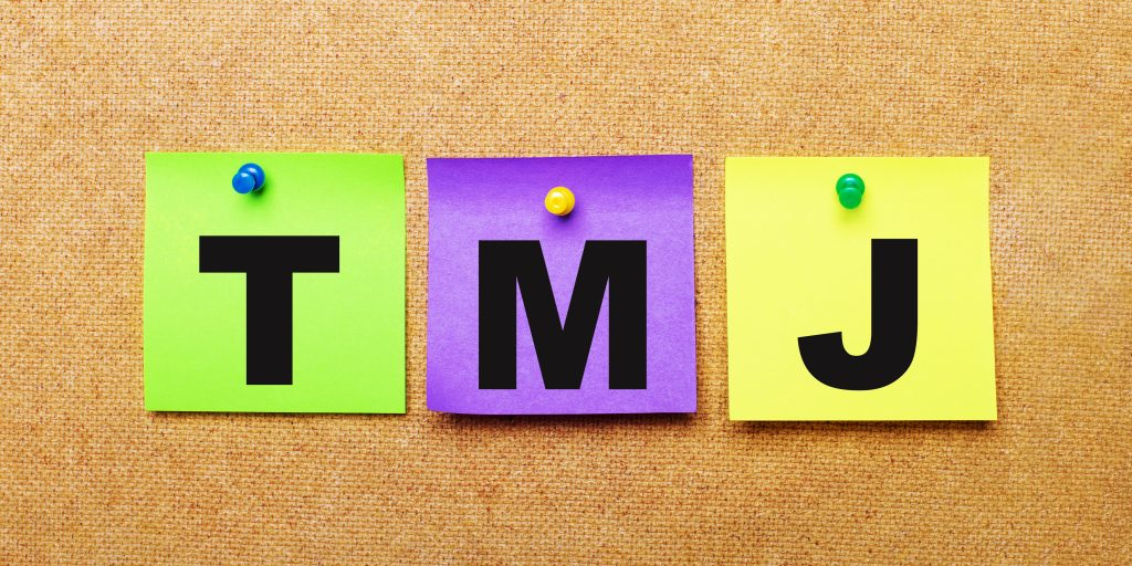 On a beige background, multi-colored stickers for notes with the word TMJ