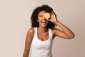 Excited african-american woman having fun with half of lemon on light background