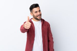 Young handsome man with beard wearing a corduroy jacket over isolated white background with thumbs up because something good has happened