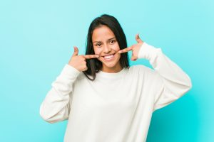 Young pretty hispanic woman smiles, pointing fingers at mouth.