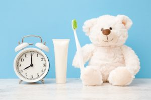 Smiling, lovely white teddy bear sitting and holding toothbrush.